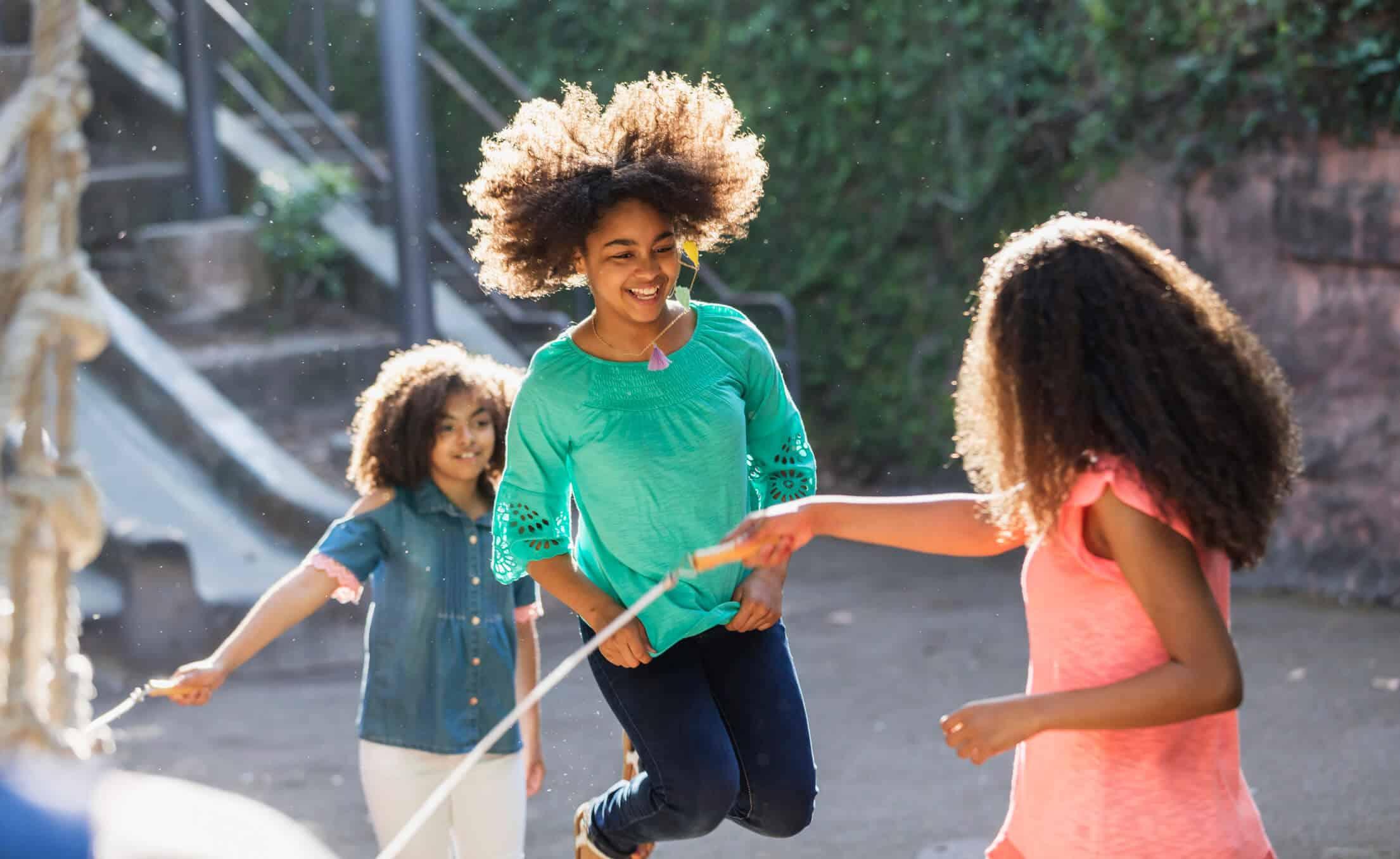 brincadeira: crianças se divertindo pulando corda em pátio de casa