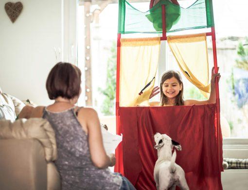 brinquedos atuais: menina brincando de fantoche com sua mãe enquanto seu cachorro observa