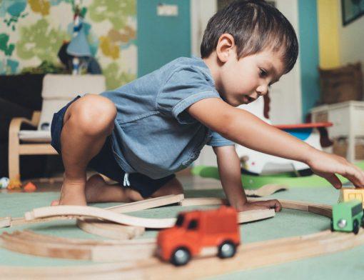 brincadeiras divertidas: menino brincando com carrinhos em seu quarto