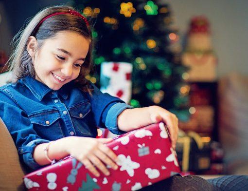 presentes de natal para crianças: criança abrindo presente perto da árvore de natal