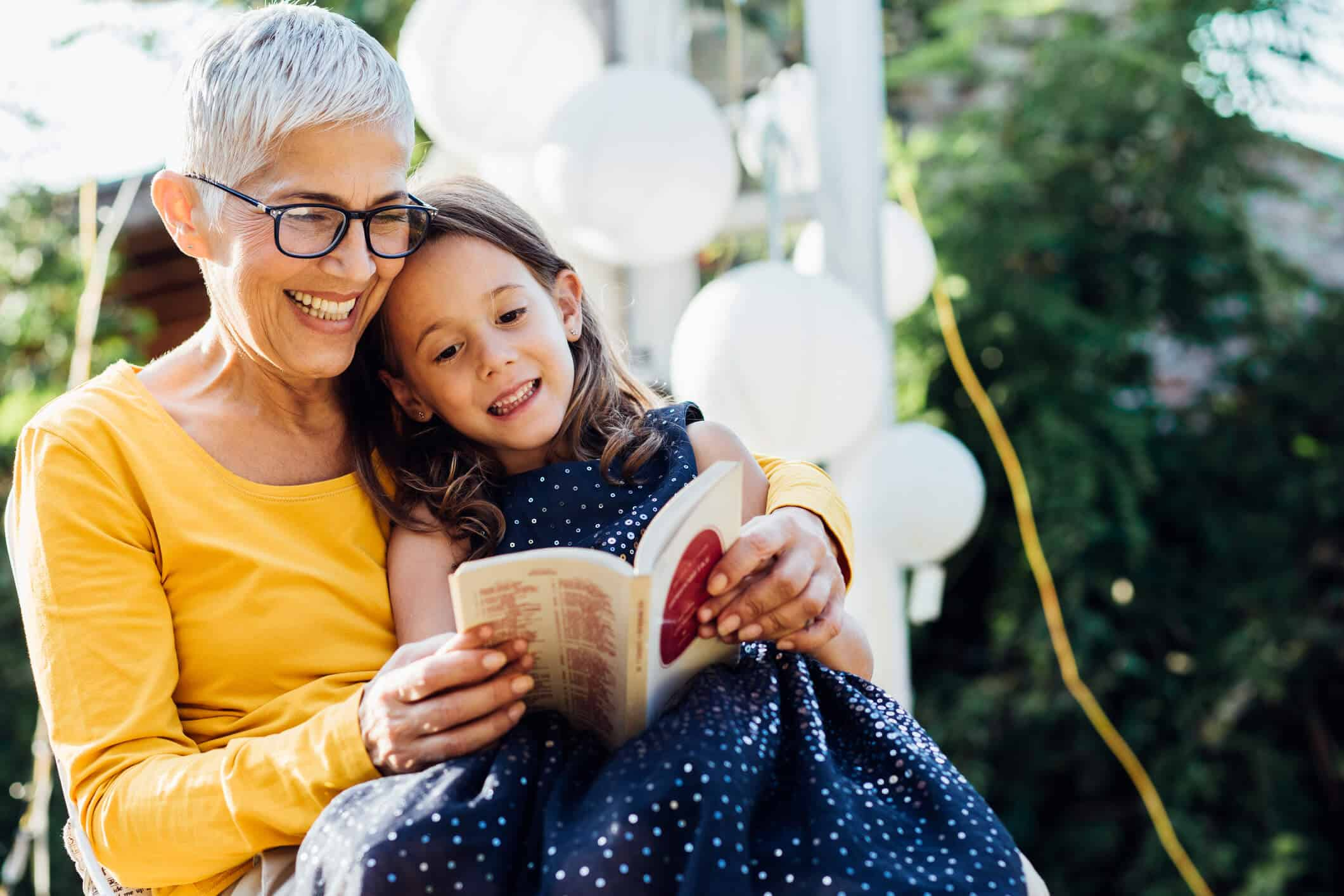 atividades para desenvolver a leitura: avó lendo para neta em jardim bonito.