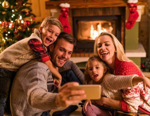 brincadeiras de natal: família comemorando o Natal em casa com lareira no fundo
